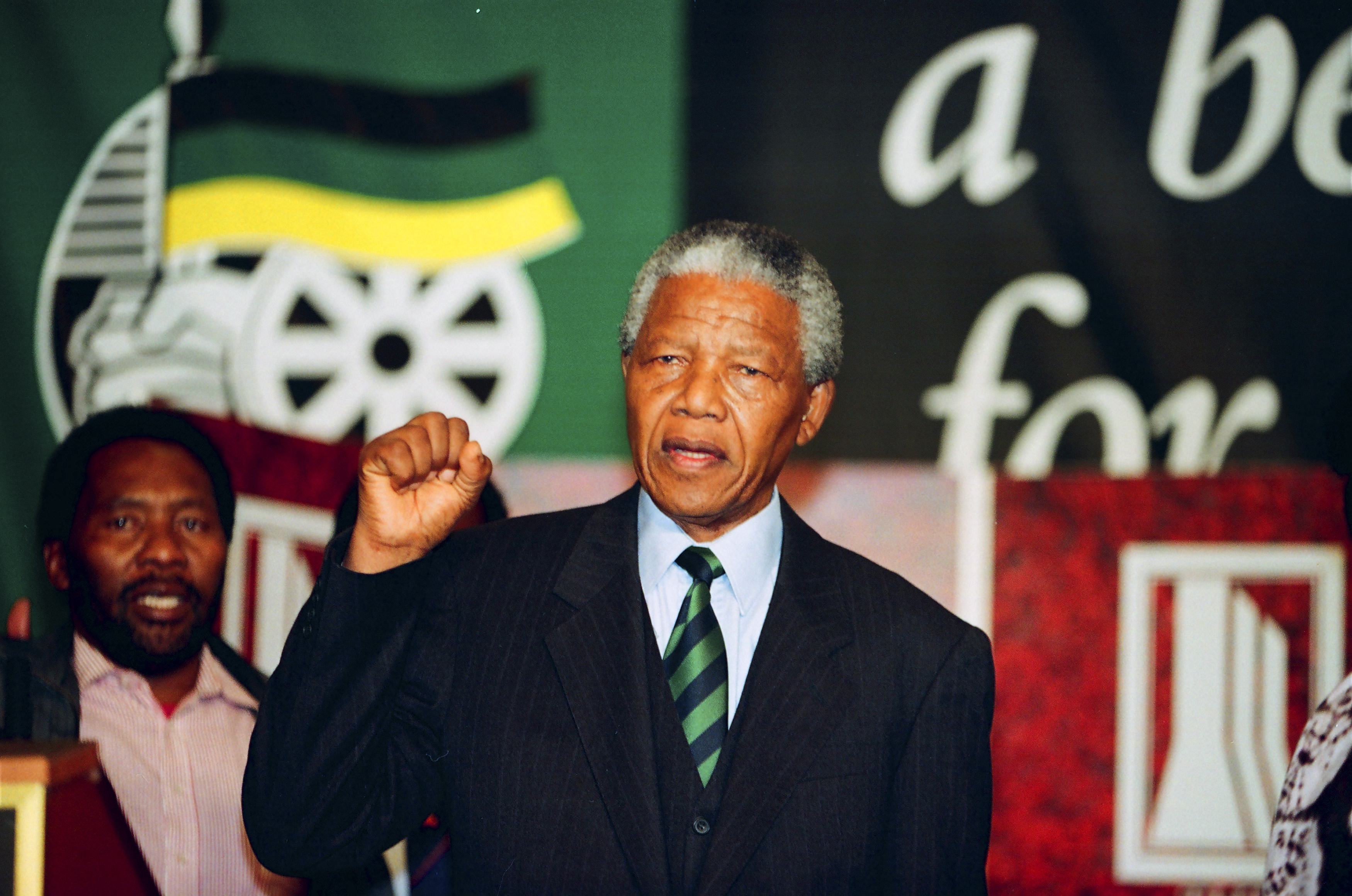 South Africa's President-elect Nelson Mandela (2nd L) holds his fist in the air at the African National Congress (ANC) following the announcement that his party had won the first free South African Presidential elections in Johannesburg May 2, 1994.  REUTERS/Peter Andrews (SOUTH AFRICA - Tags: POLITICS ELECTIONS) - RTX114R5