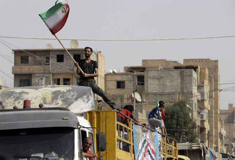 A Syrian man holds the Iranian flag as a convoy carrying aid provided by Iran arrives in the eastern city of Deir Ezzor on September 20, 2017 while Syrian government forces continue to press forward with Russian air cover in the offensive against Islamic State group jihadists across the province. Two separate offensives are under way against the jihadists in the area -- one by the US-backed Syrian Democratic Forces, the other by Russian-backed government forces. The Syrian army now controls around 70 percent of the city and is battling to oust IS from the remainder, according to the Britain-based Observatory.  / AFP PHOTO / LOUAI BESHARA        (Photo credit should read LOUAI BESHARA/AFP/Getty Images)