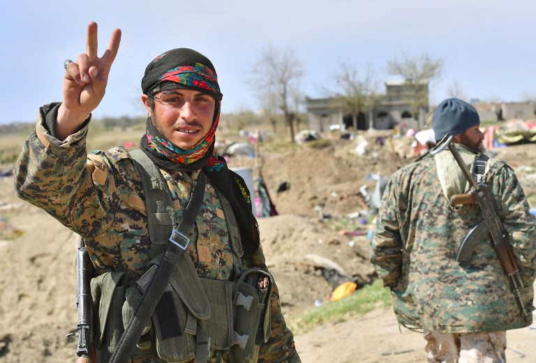 """A picture taken on March 23, 2019 shows a fighter of the US-backed Kurdish-led Syrian Democratic Forces (SDF) flashing the V for victory sign in the fallen Islamic State group's last bastion in the eastern Syrian village of Baghuz after defeating the jihadist group. - Kurdish-led forces pronounced the death of the Islamic State group's nearly five-year-old """"caliphate"""" on March 23, 2019 after flushing out diehard jihadists from their very last bastion in eastern Syria. (Photo by GIUSEPPE CACACE / AFP)"""