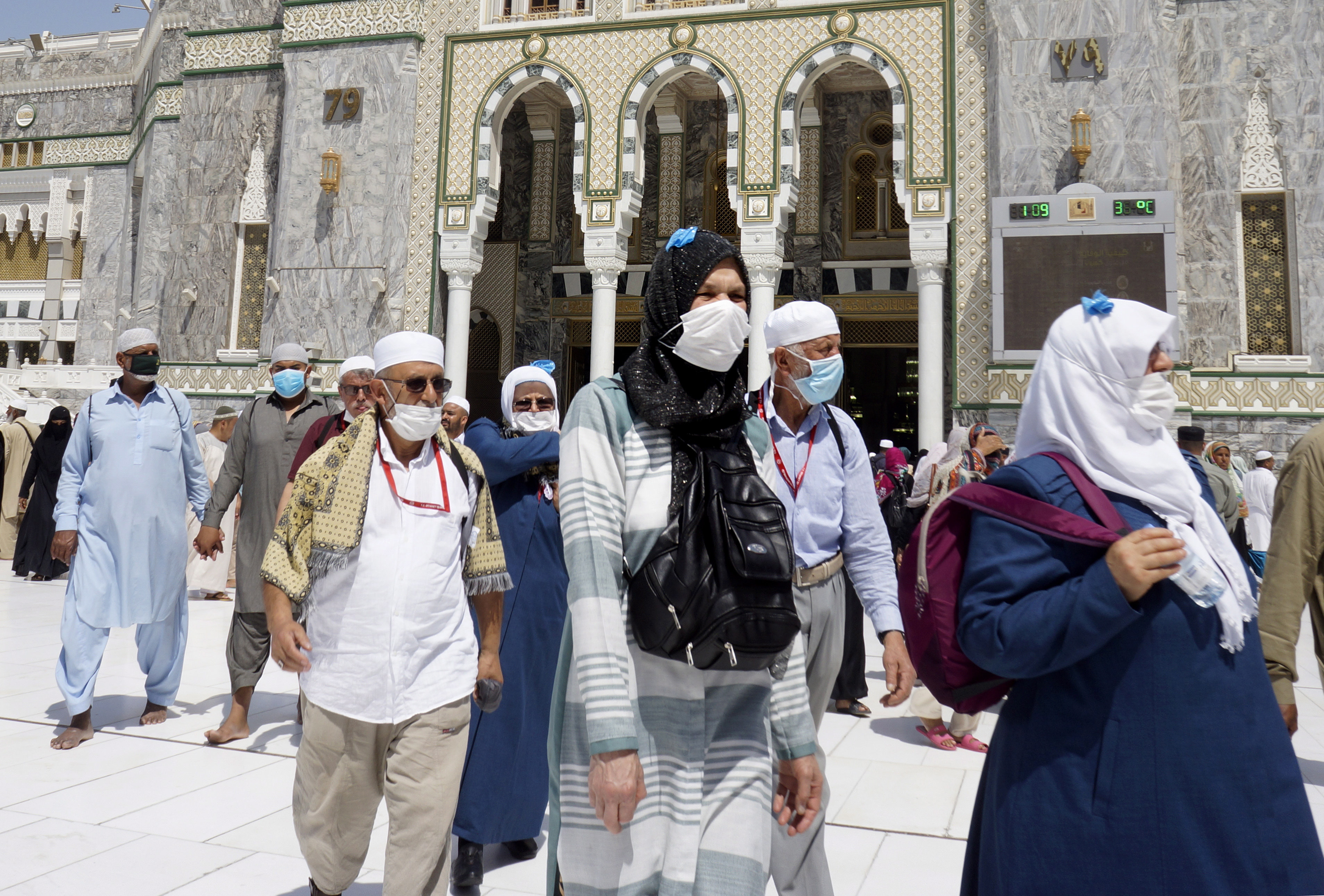 Muslim worshippers wear masks after the noon prayers outside the Grand Mosque, in the Muslim holy city of Mecca, Saudi Arabia, Saturday, March 7, 2020. Saudi Arabia announced there would be no spectators for sports competitions and games starting Saturday in order to combat the spread of the virus. The kingdom has five confirmed cases, but has taken unprecedented measures against the virus' spread, including halting all pilgrimage in Mecca, Islam's holiest site. (AP Photo/Amr Nabil)